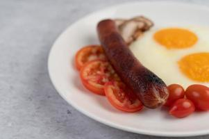 Breakfast plate with fried eggs, tomatoes, Chinese sausage and mushrooms