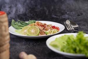 Ensalada picante de cerdo con lima sobre una cama de verduras foto