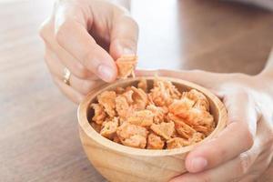 Close-up de una persona comiendo camarones fritos