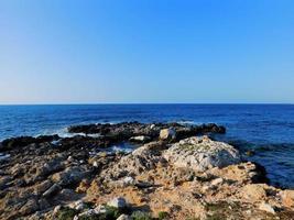 frente al mar rocoso con agua azul foto