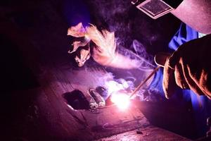 Welder in blue uniform welding the workpiece photo