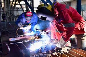 Welder in red uniform welding the workpiece
