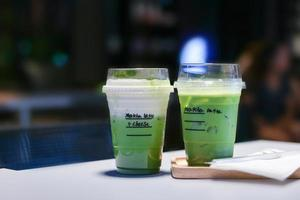 Iced matcha green tea latte on table in store.