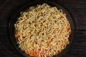Instant noodles in bowl on wooden background.