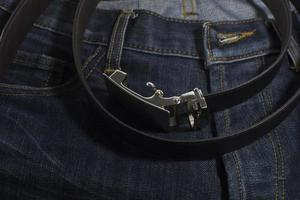 Detail of jeans with black leather belt closeup.