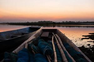 Barco de madera amarrado en un río al atardecer