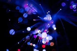 La colorida luz púrpura del bokeh celebra en la noche, desenfoque de fondo abstracto claro.