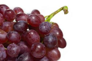 Uva roja madura con racimo aislado sobre fondo blanco.