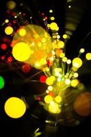 La luz colorida del bokeh celebra en la noche, desenfoca el fondo amarillo abstracto ligero.