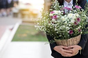 Woman carrying a bouquet of flowers.