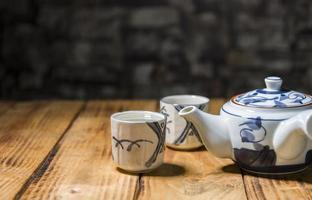 Teapot and two teacups on the old wooden table photo