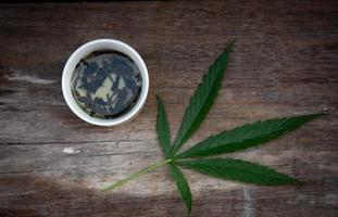 Green marijuana leaves and marijuana tea cup photo