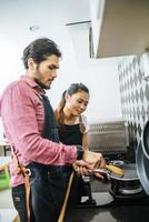 A happy young couple cooking together at home photo