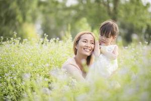 Mother and little daughter playing together in a meadow