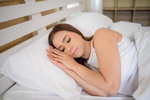 Mujer joven duerme en el dormitorio, acostado en la cama foto