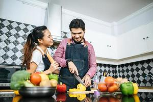 Happy young couple preparing food for cooking in kitchen at home photo