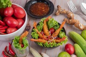 Shrimp deep fried in batter on salad photo