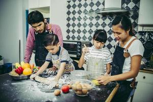 Happy family enjoying their time cooking together in the kitchen photo