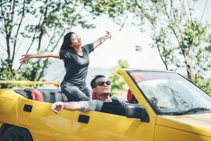 Happy couple enjoying the top down in convertible photo