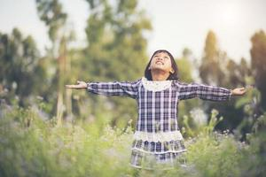 Little girl raising her hands in the fresh air