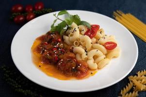 macarrones salteados con tomate, chile, semillas de pimiento y albahaca