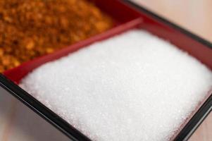 azúcar blanca en una taza junto a hojuelas de pimiento rojo foto