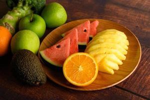 sandía de colores, piña, naranjas con aguacate y manzanas