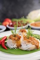 Rice noodle noodles topped with coconut milk and vegetables photo