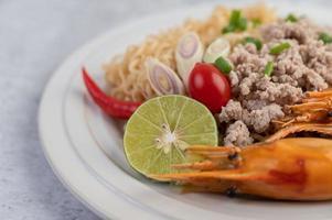 fideos y camarones en un plato blanco foto