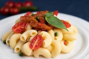 Stir-fried macaroni with tomato, chili, pepper seeds and basil