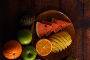 Colorful watermelon, pineapple, oranges with avocado and apples photo