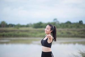 Healthy young woman warming up outdoors for training photo