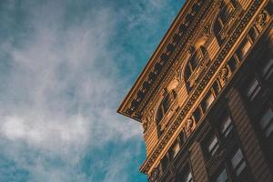 Corner of brown building with cloudy blue sky