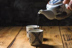 Human's hand holding the teapot and two teacups photo
