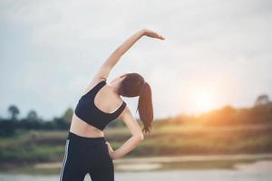 Mujer joven sana calentando al aire libre para entrenar