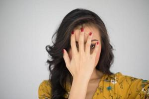 Beautiful young woman covers face with her hands