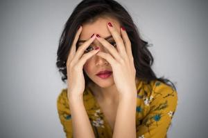 Beautiful young woman covers her face with hands
