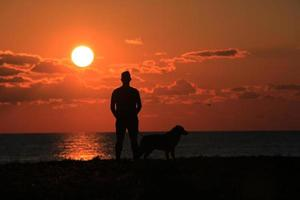 Silhouette of man and dog at sunset photo