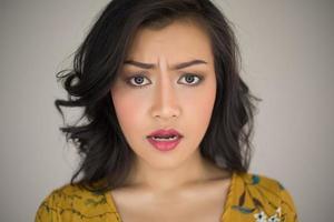 Mujer joven haciendo expresión facial sobre fondo blanco. foto