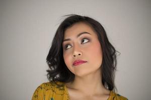 mujer joven hace la expresión facial sobre fondo blanco foto