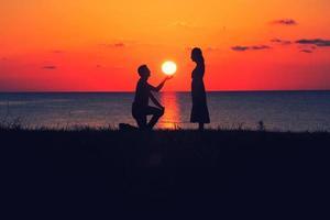 Man proposing at sunset photo
