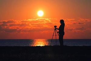 A photographer woman looking at the sunset