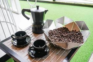 Italian metallic coffee maker with coffee beans and black coffee cup on wooden table. Mocha coffee pot for making espresso coffee