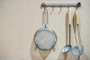 Kitchen cooking utensils on steel rack. steel spatulas etc against rustic wooden wall with copy space photo