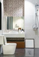 Modern spacious bathroom with bright tiles with glass shower, toiletasas and sink. Side view