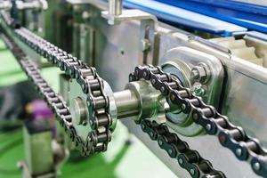 Gear and chain drive shaft in conveyor chain, and conveyor belt is on production line. photo