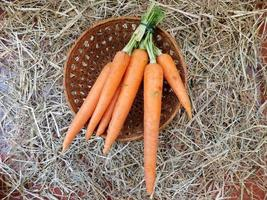 Carrots in a basket with a straw background
