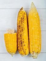 Vista superior de mazorcas de maíz enteras y cortadas sobre fondo de madera