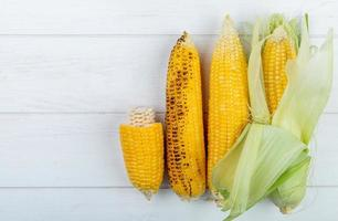 Vista superior de mazorcas de maíz enteras y cortadas sobre fondo de madera con espacio de copia