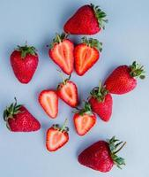 Top view of whole and cut strawberries photo